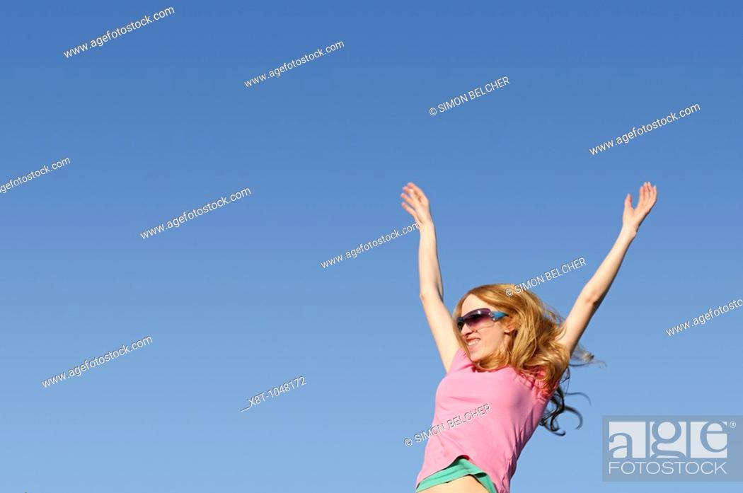 Stock Photo: Woman With Arms Raised, Against a Blue Sky.
