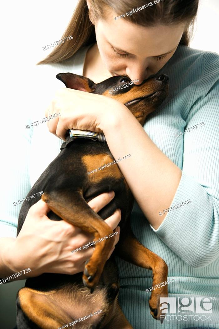 Stock Photo: Caucasian woman holding and kissing Miniature Pinscher dog.