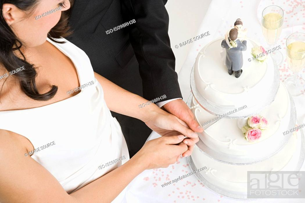 Stock Photo: Bride and groom cutting a wedding cake.