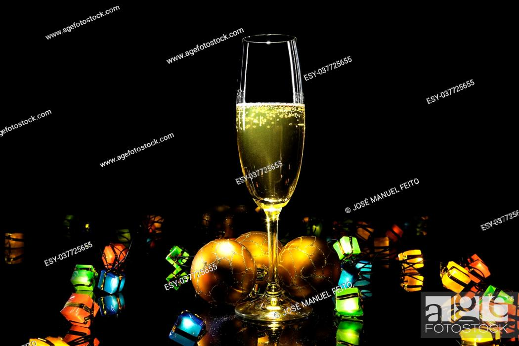 Stock Photo: champagne glass with Christmas balls, Christmas lights on black background.