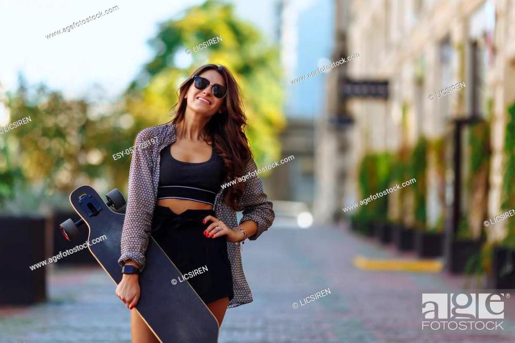 Stock Photo: Beautiful young woman with longboard on the city street in sunny weather. Young hipster girl posing with longboard, skateboard, streetphoto, life style, freedom.
