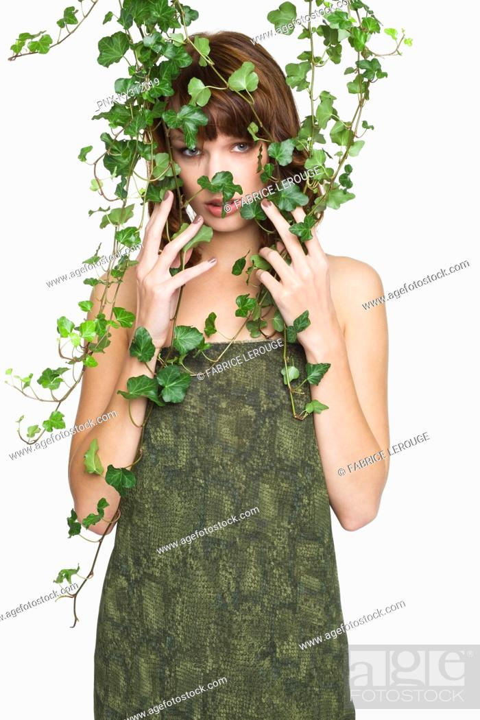 Stock Photo: Woman with ivy covering her face.