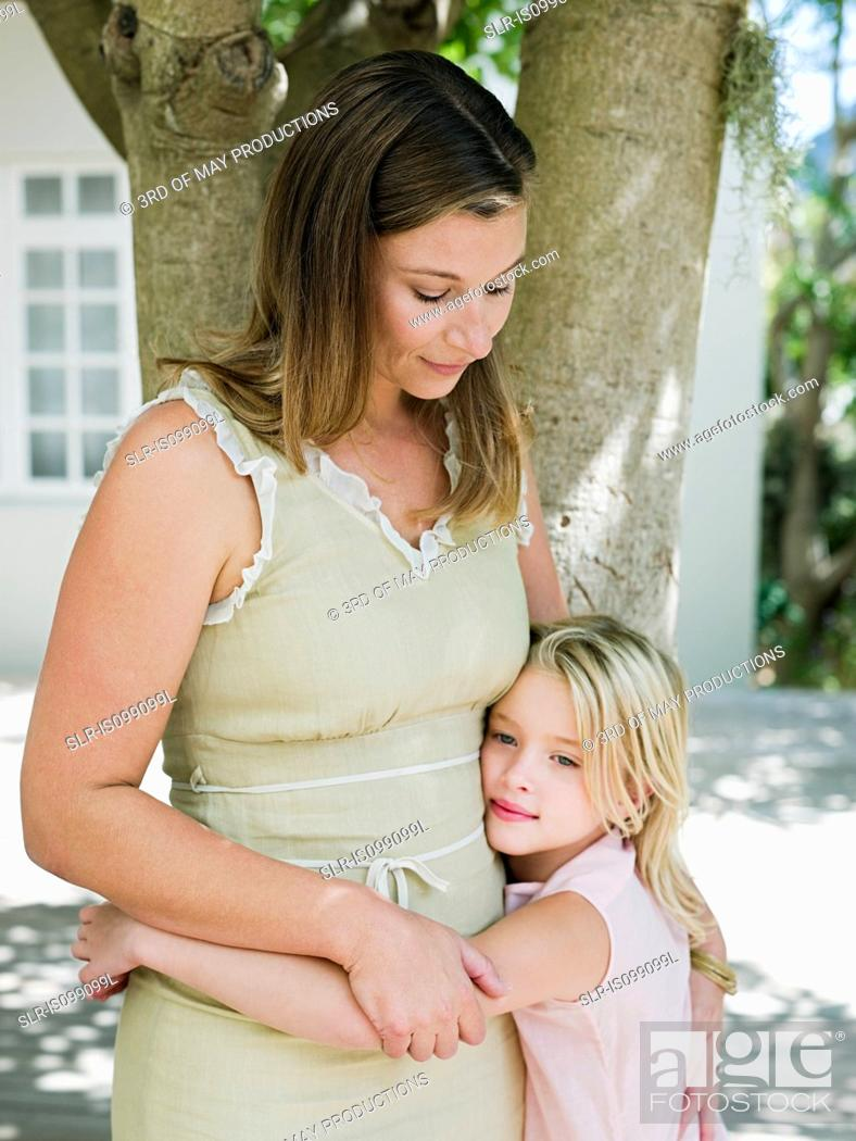Stock Photo: Mother and daughter embracing by tree.
