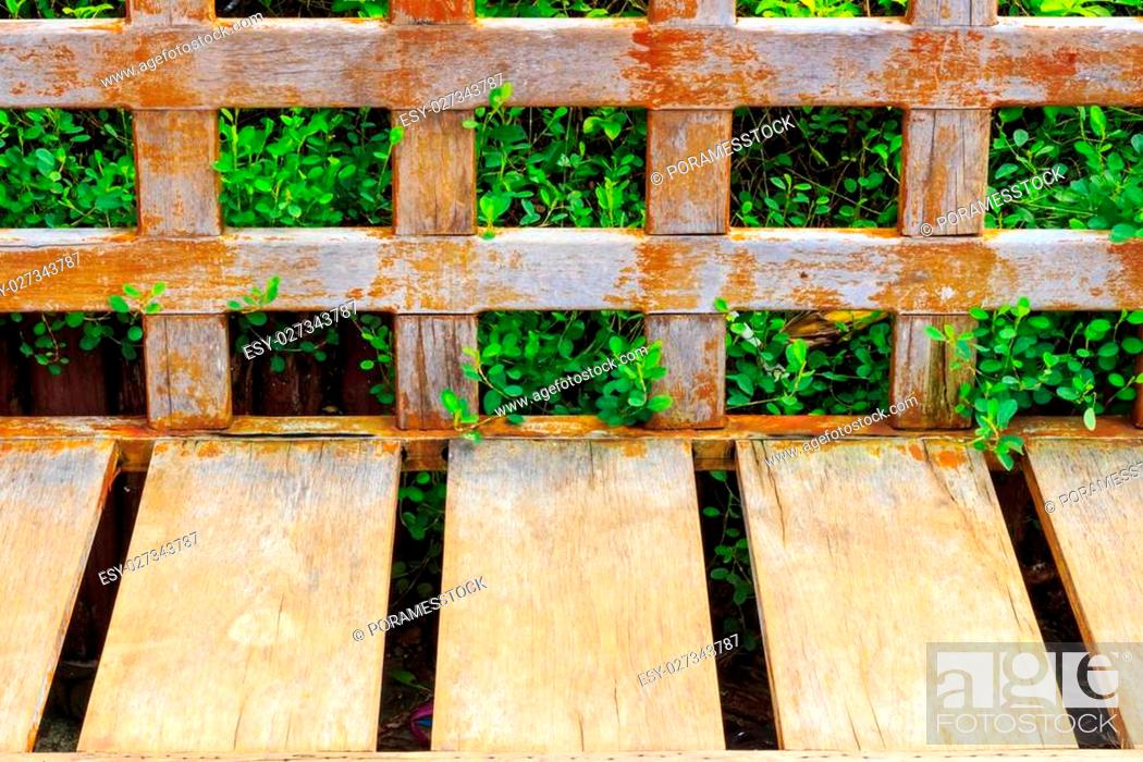 Stock Photo: Old Wood long arms chair on plant background and brick floor.