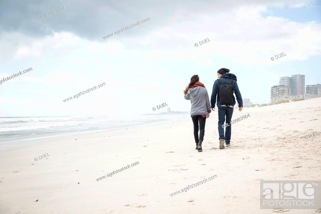 Stock Photo: Rear view of young couple strolling on beach, Western Cape, South Africa.