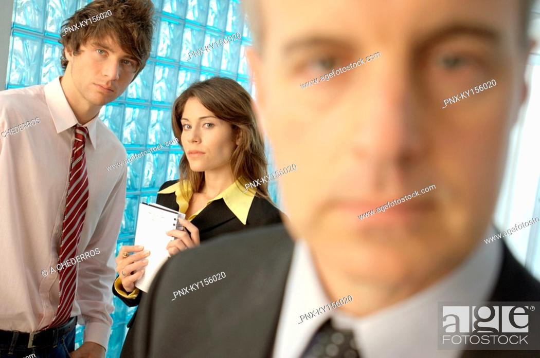 Stock Photo: Businessman in office with colleagues in background.