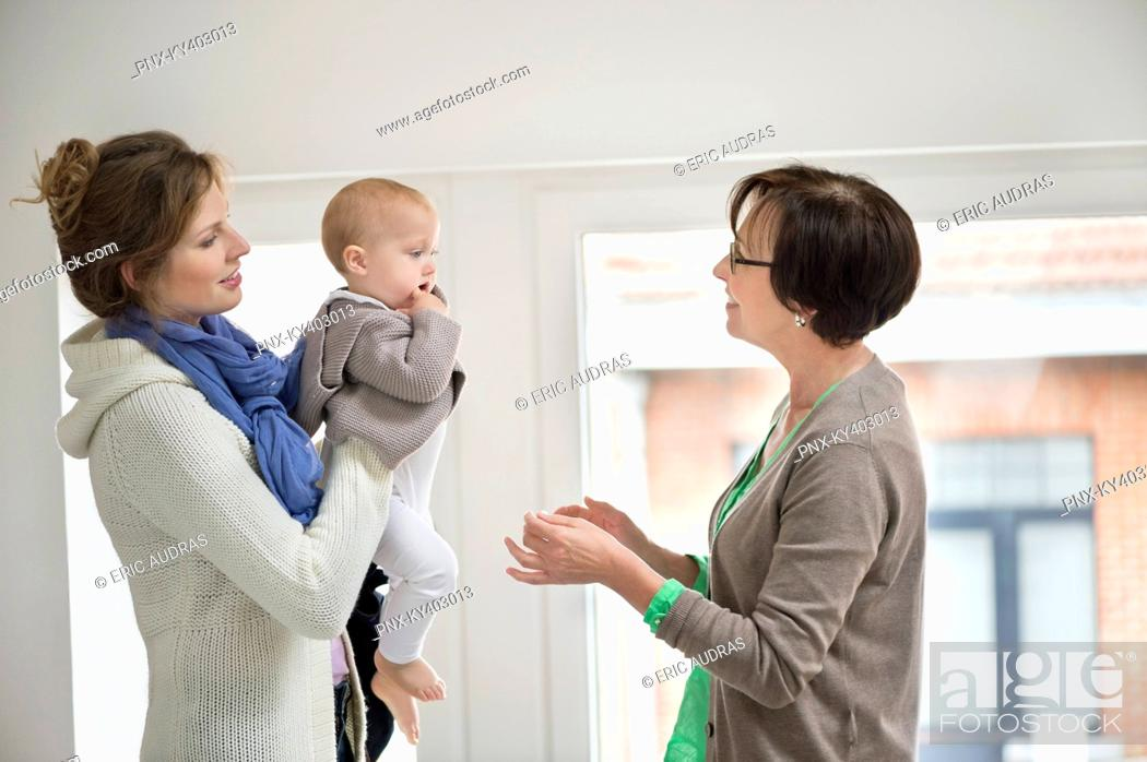 Stock Photo: Woman giving her daughter to nanny.