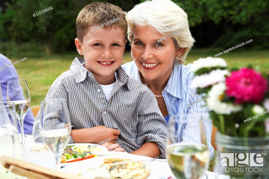Stock Photo: Grandmother with grandson 7-9 on lap sitting at table in garden.