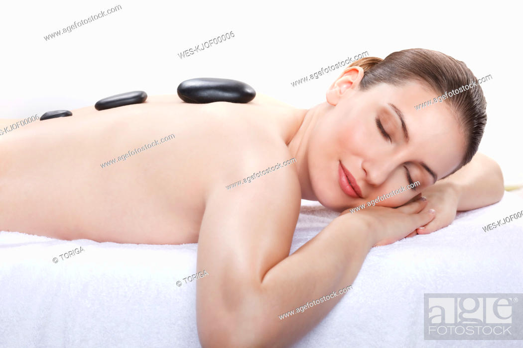 Stock Photo: Woman having a hot stone treatment, smiling, eyes closed.