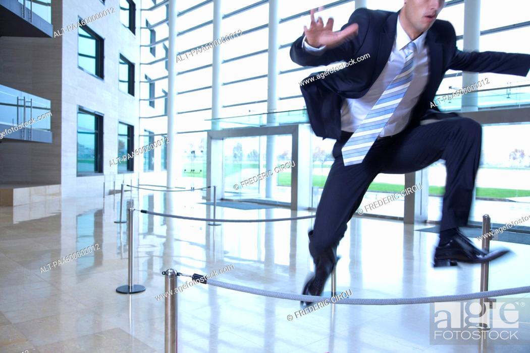Stock Photo: Businessman jumping over ropes in lobby.