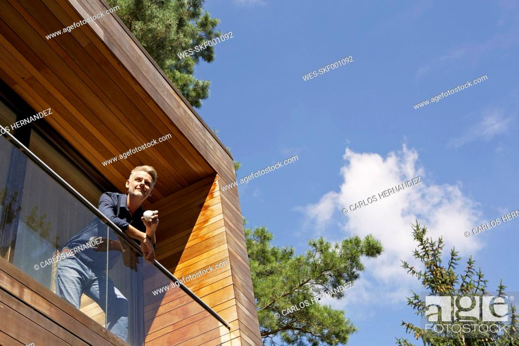 Stock Photo: Germany, Berlin, Mature man standing on balcony and relaxing.