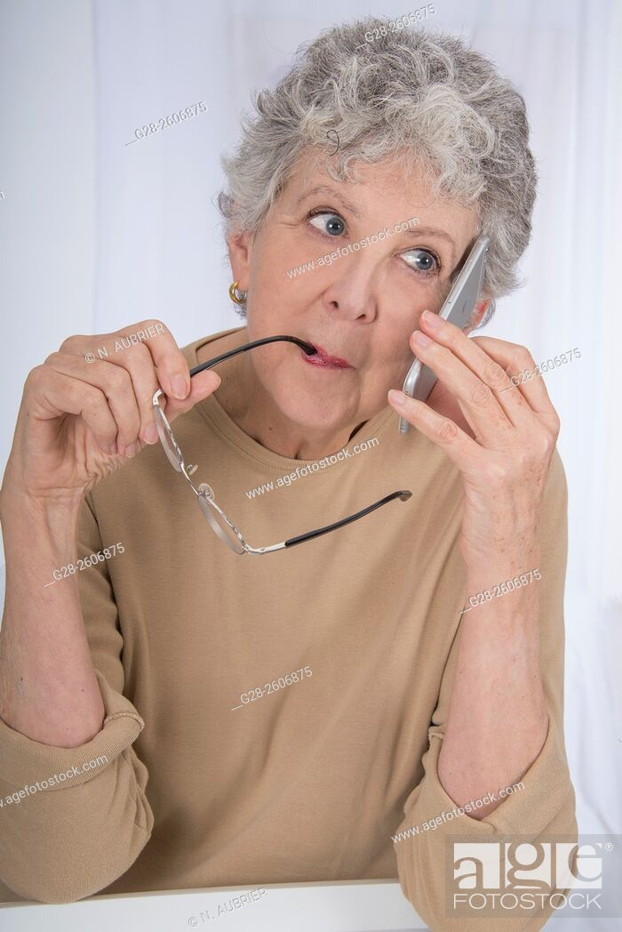 Stock Photo: Thoughtful senior woman with grey hair, biting her glasses and using a mobile phone.