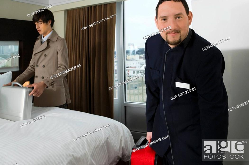 Stock Photo: Portrait of a room service man holding a luggage with a businessman looking at a briefcase.