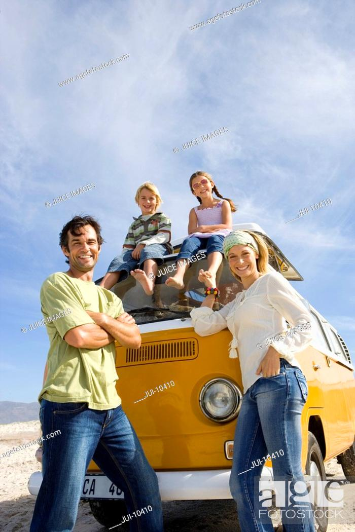 Stock Photo: Family of four, parents by son and daughter 5-9 on roof of camper van, smiling, portrait, low angle view.