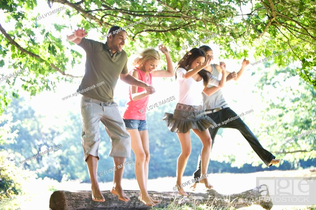 Stock Photo: Four young people jumping from a log.