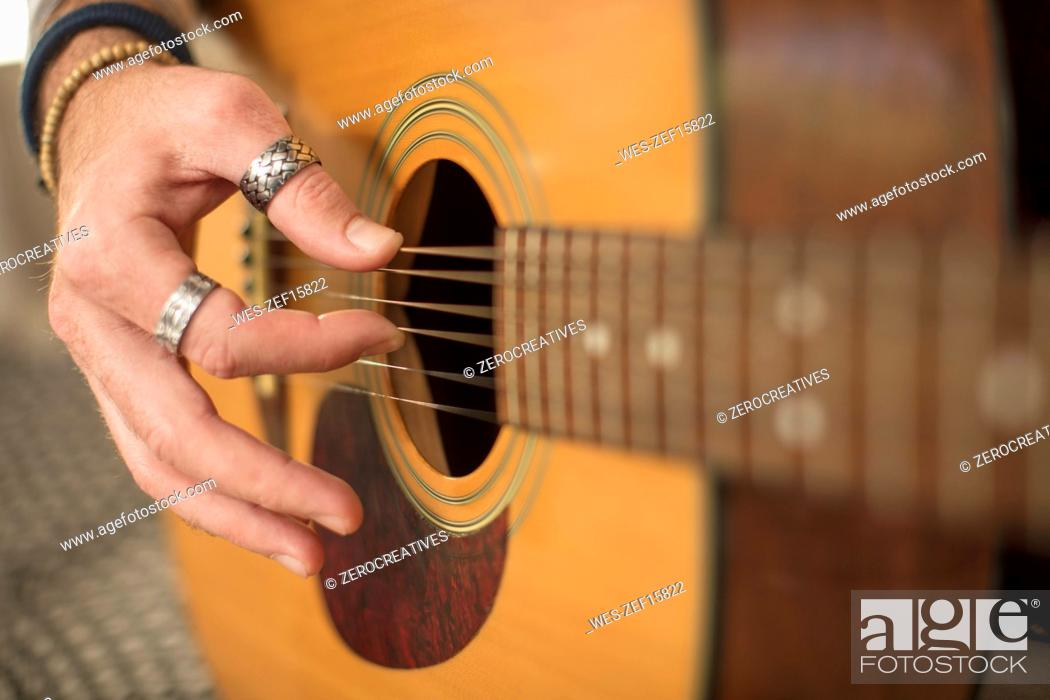 Imagen: Close-up of man's hand playing guitar.