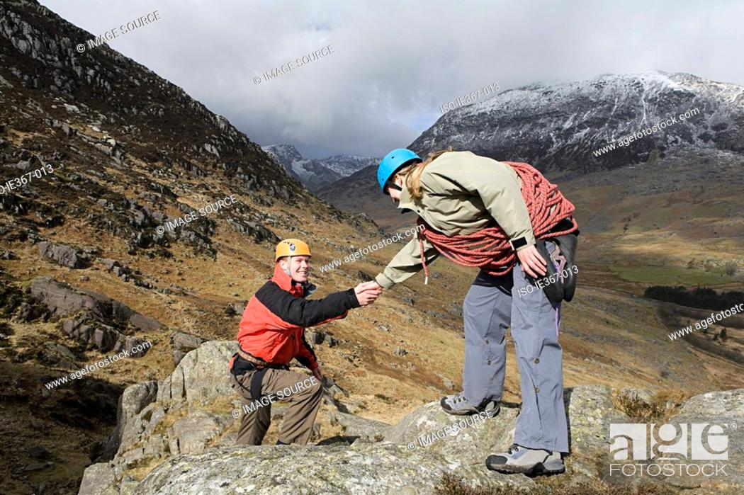 Stock Photo: A woman giving a man a helping hand.