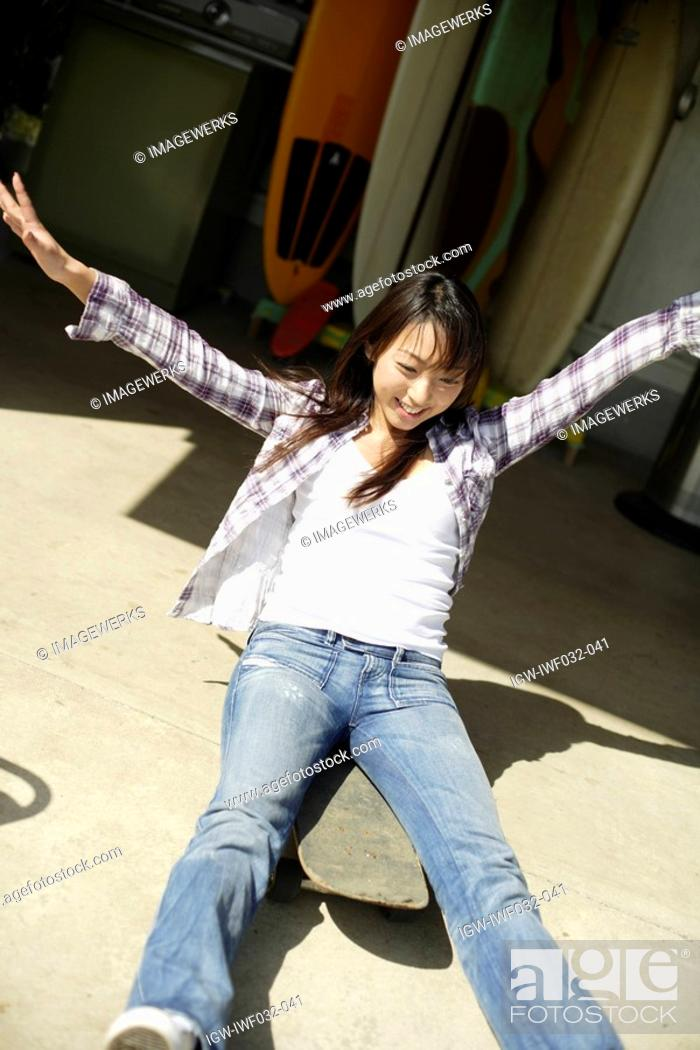Stock Photo: View of a young woman sitting on the skateboard with arms outstretched.