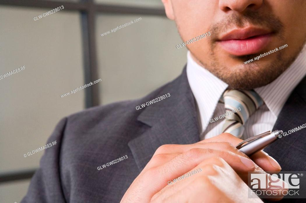 Stock Photo: Close-up of a businessman holding a pen.