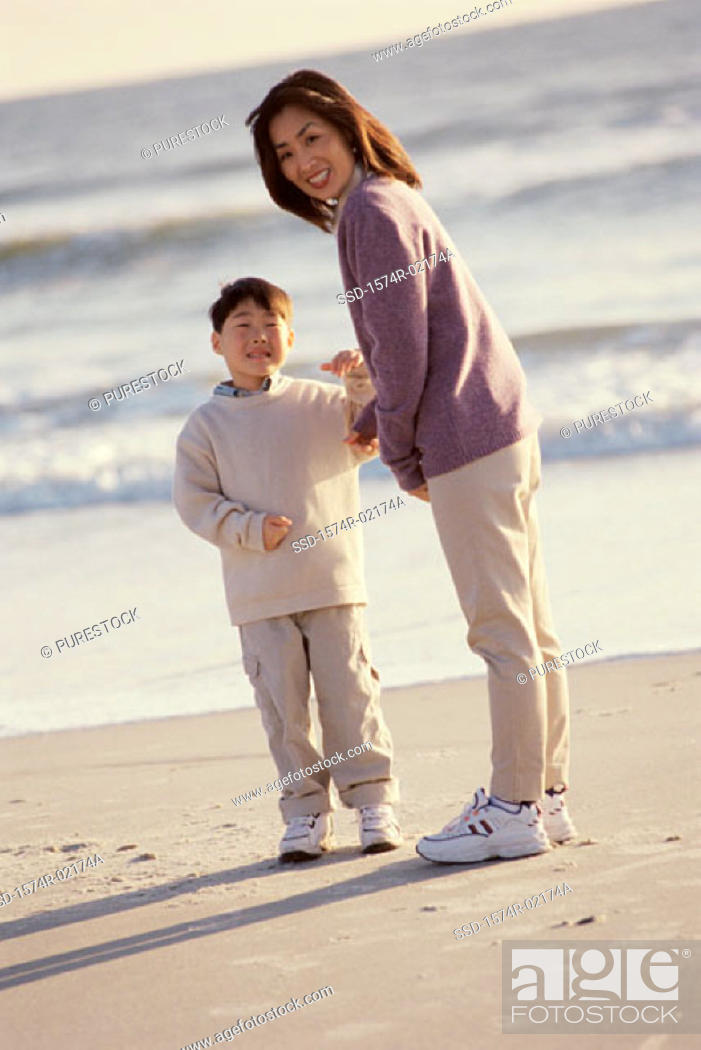 Stock Photo: Portrait of a mother and her son standing on the beach.