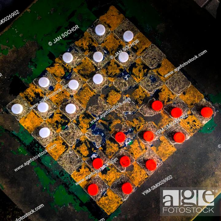 Stock Photo: Plastic bottle caps (checkers pieces) are seen positioned before the game begins on an outdoor checkerboard table in the park in San Salvador, El Salvador.