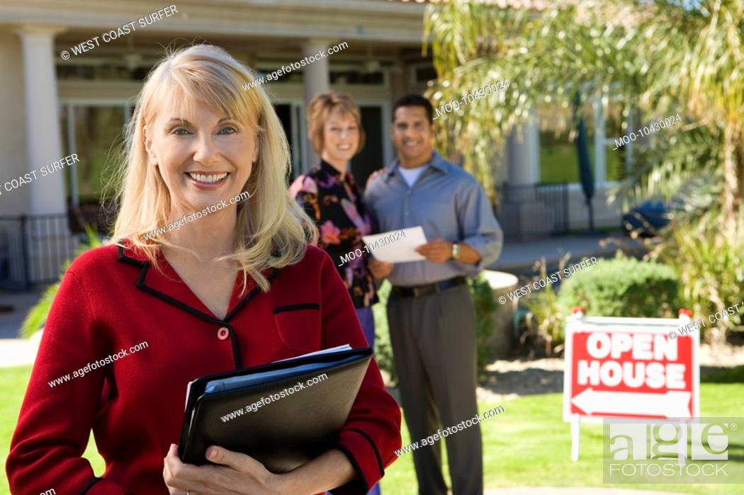 Stock Photo: Portrait of smiling estate agent with house and home buyers in background.