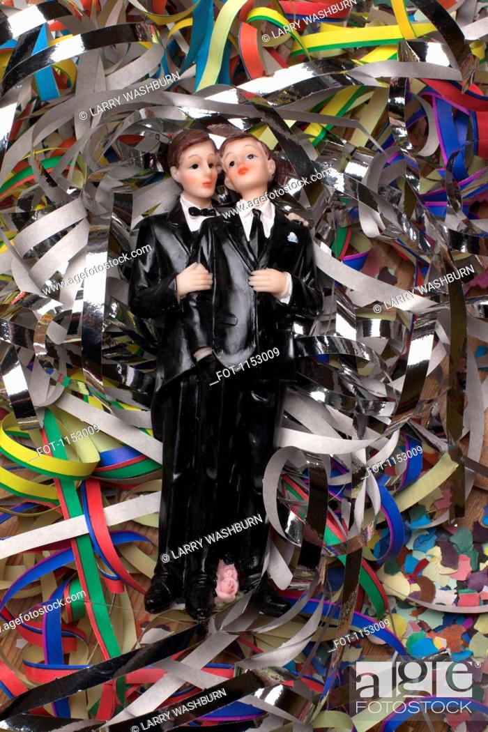 Stock Photo: Two male figurines lying on confetti and streamers.
