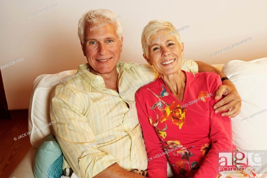 Stock Photo: Portrait of a mature man and a senior woman sitting on a couch and smiling.