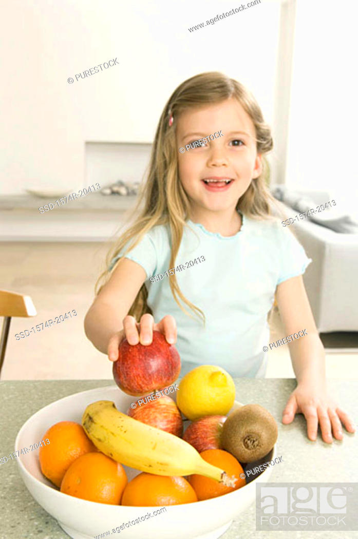 Stock Photo: Portrait of a girl picking up an apple from a fruit bowl.