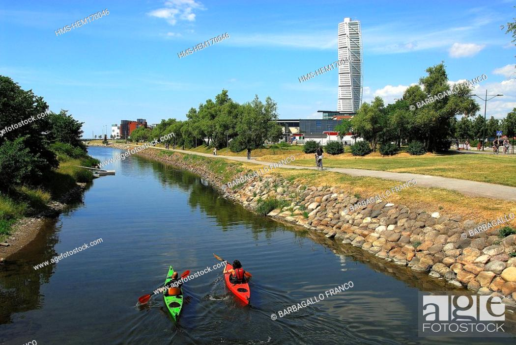 Stock Photo: Sweden, Skane County, Malmo, sea kayaking along city canals and the Turning Torso tower by architect Santiago Calatrava in the background.