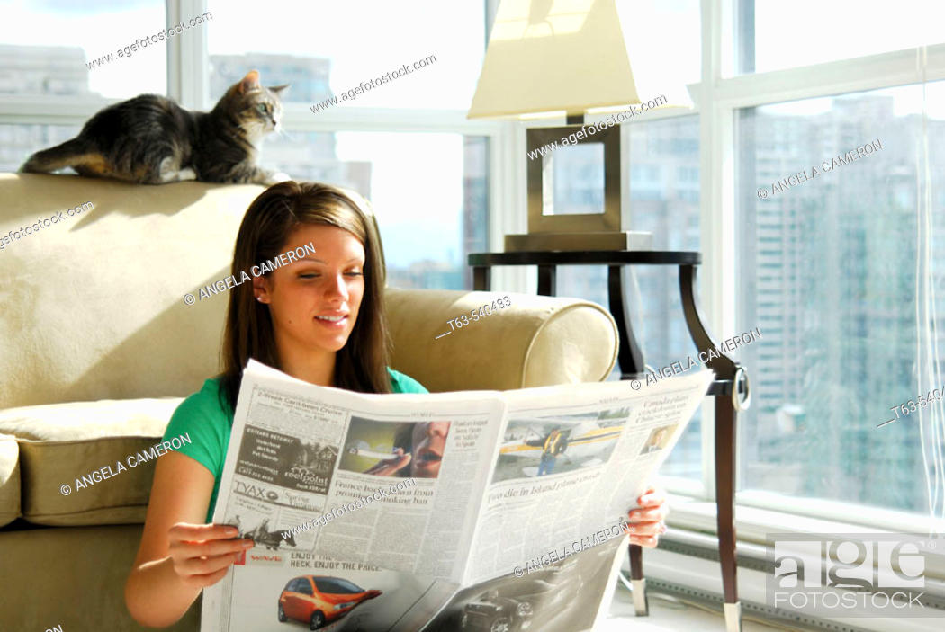 Stock Photo: 20 yr old young woman sitting in apartment reading newspaper.
