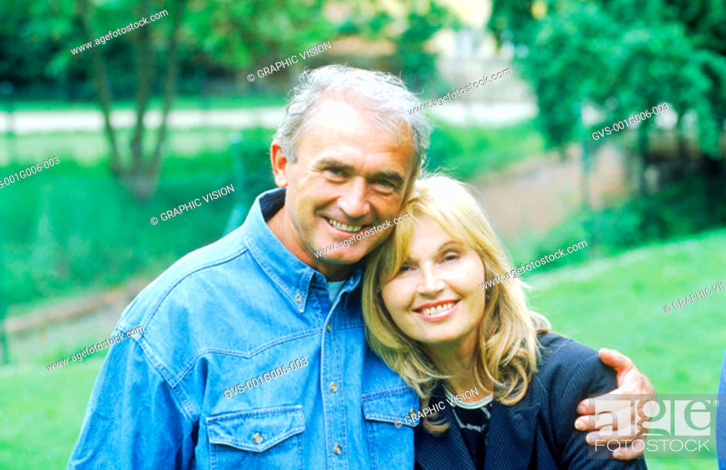 Stock Photo: Portrait of mature couple standing in a lawn.