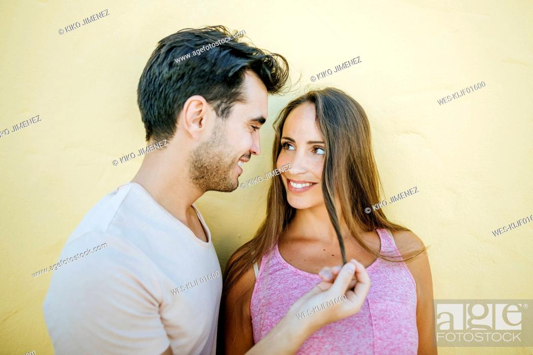 Stock Photo: Young couple looking at each other in love against yellow wall.