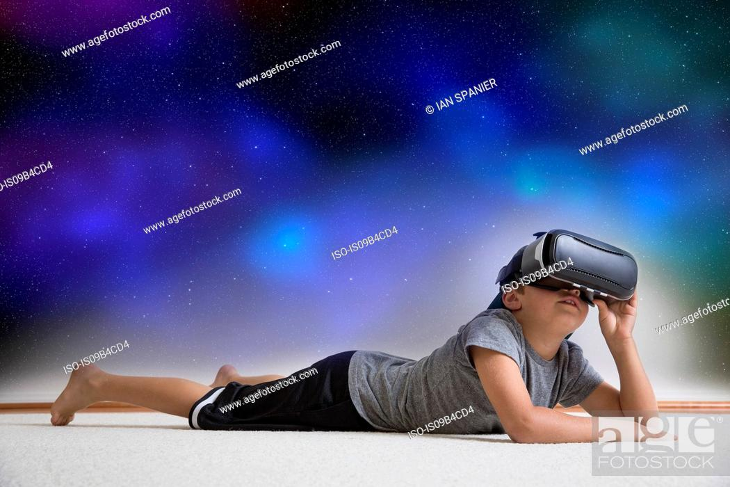 Stock Photo: Young boy lying on floor, wearing virtual reality headset, looking into night sky, digital composite.