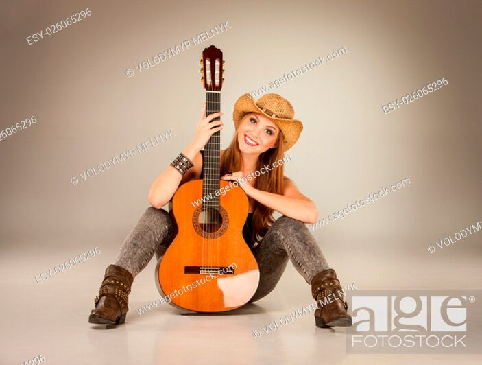 Stock Photo: The beautiful girl in a cowboy's hat and acoustic guitar on a gray background.