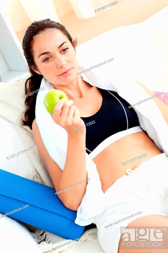 Stock Photo: Athletic young woman holding a appl.