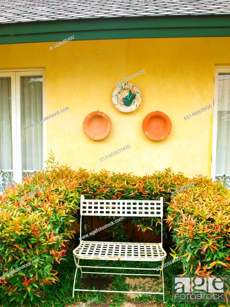 Stock Photo: A metal bench in a garden on yellow wall background.