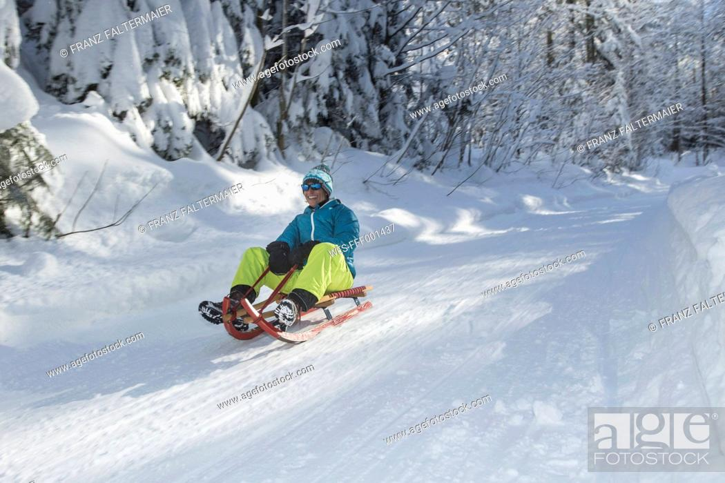 Stock Photo: Germany, Bavaria, Inzell, man having fun on a sledge in snow-covered landscape.