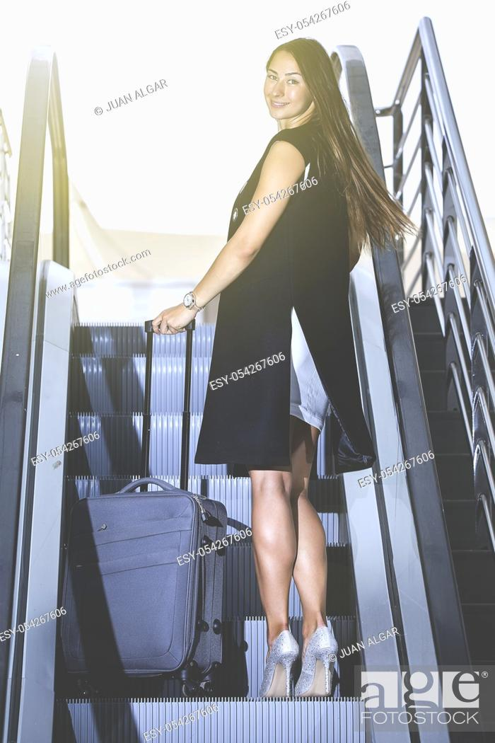 Stock Photo: Back view of young stylish businesswoman with luggage on moving stairs looking at camera over shoulder.