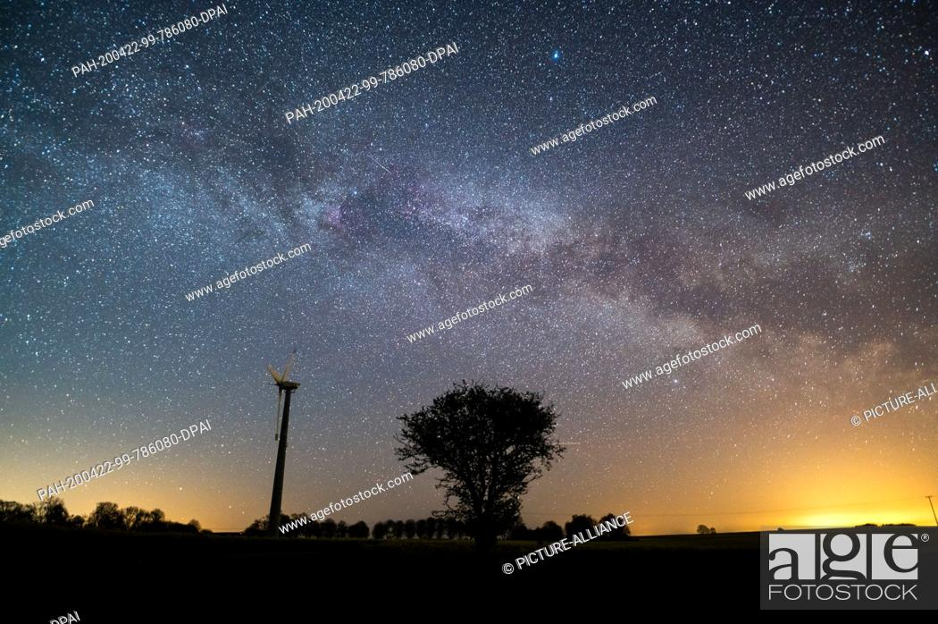 Stock Photo: 22 April 2020, Schleswig-Holstein, Neukirchen: The starry sky shines above a tree and a windmill. Mostly starry skies currently allow a clear view of the.