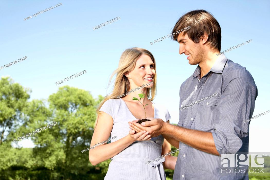 Stock Photo: Germany, Cologne, Young couple holding seedling.
