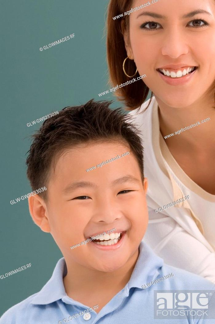 Stock Photo: Portrait of a schoolboy with his female teacher smiling together in a classroom.