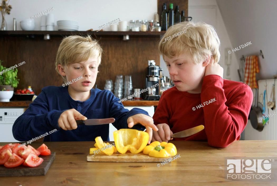Stock Photo: Boy assisting brother to chop bell pepper at table in kitchen.