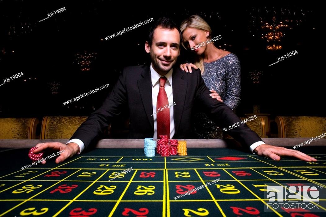 Stock Photo: Woman by man gambling at roulette table, portrait, low angle view.