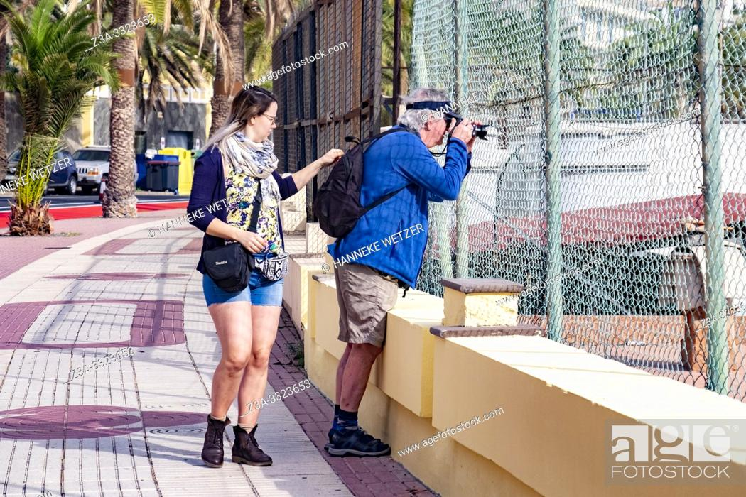 Stock Photo: Daughter zipping the bag of her dad while he is photographing in Las Palmas de Gran Canaria, Canary Islands.