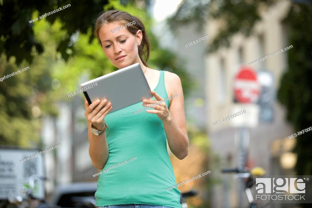 Stock Photo: Germany, North Rhine Westphalia, Cologne, Young woman with digital tablet.