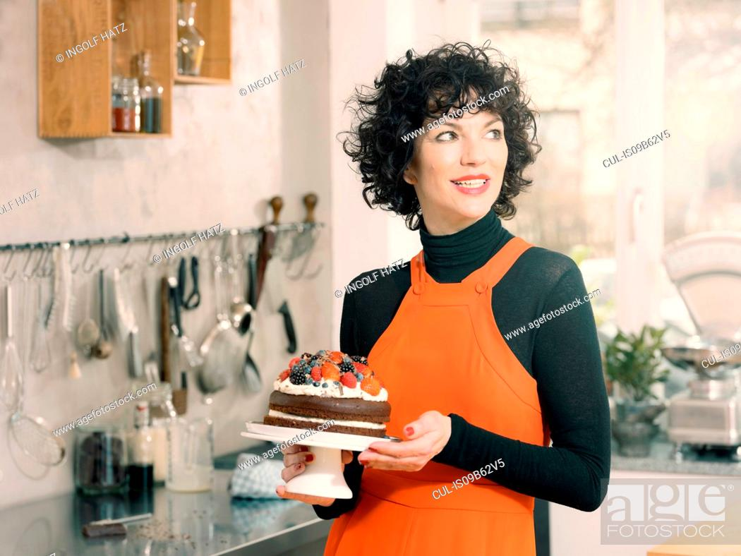 Stock Photo: Woman holding chocolate cake decorated with fresh summer fruits.