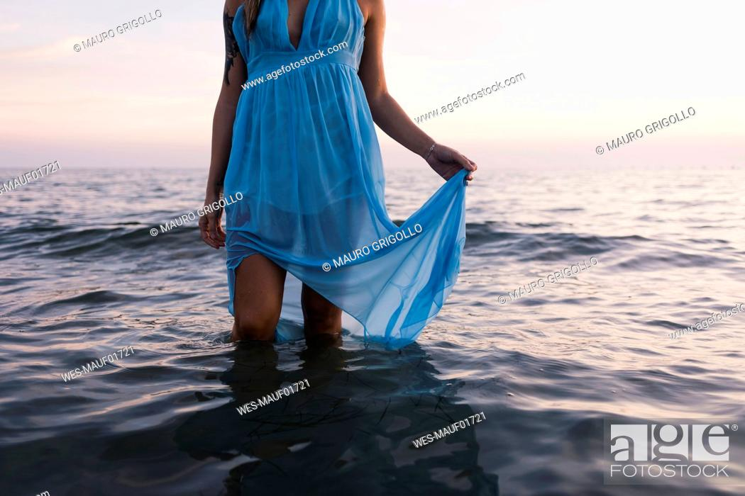 Stock Photo: Young tattooed woman wearing blue dress standing in the sea by sunset, partial view.