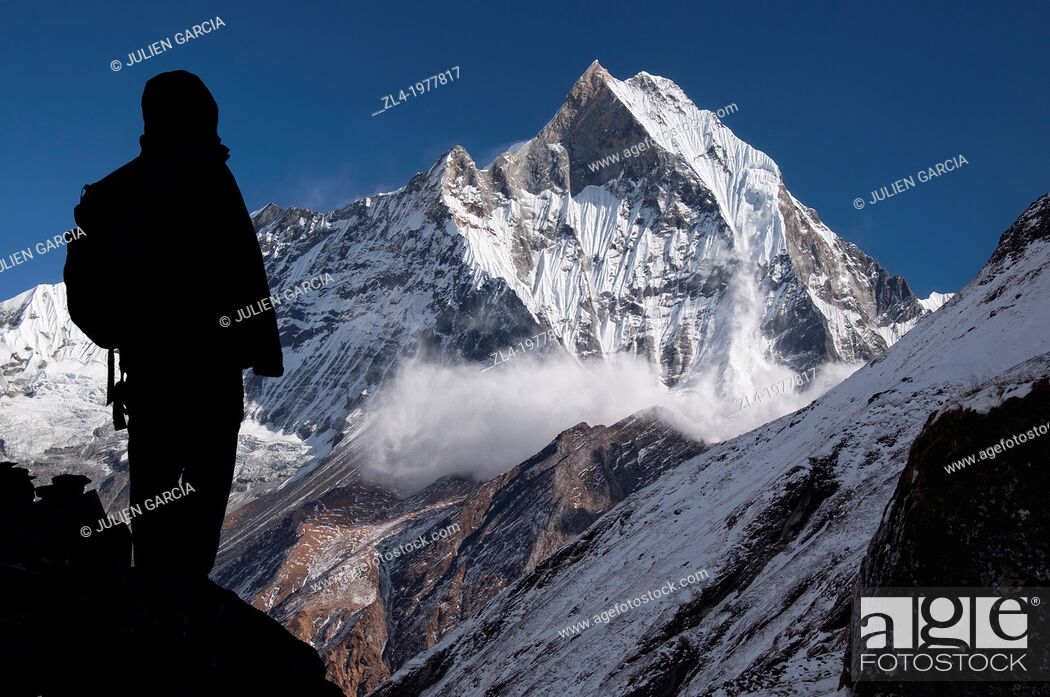 Stock Photo: Avalanche on the holy Machapuchare mountain viewed from Annapurna Base Camp, silhouette of a trekker in the foreground. Nepal, Gandaki, Annapurna.