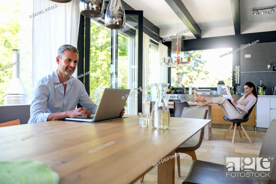 Stock Photo: Smiling man at home using a laptop at table with woman in background reading newspaper.